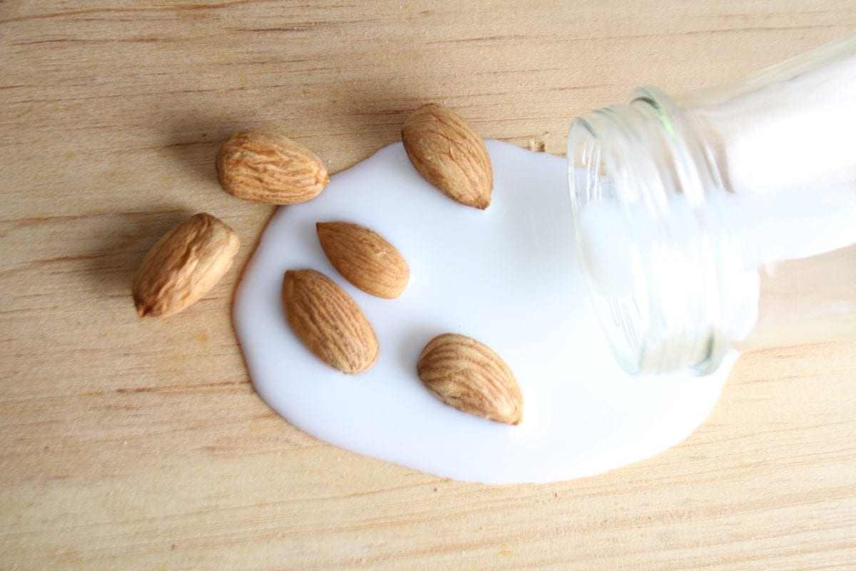 Almond milk being poured out of class bottle on to wooden surface with almonds in it.