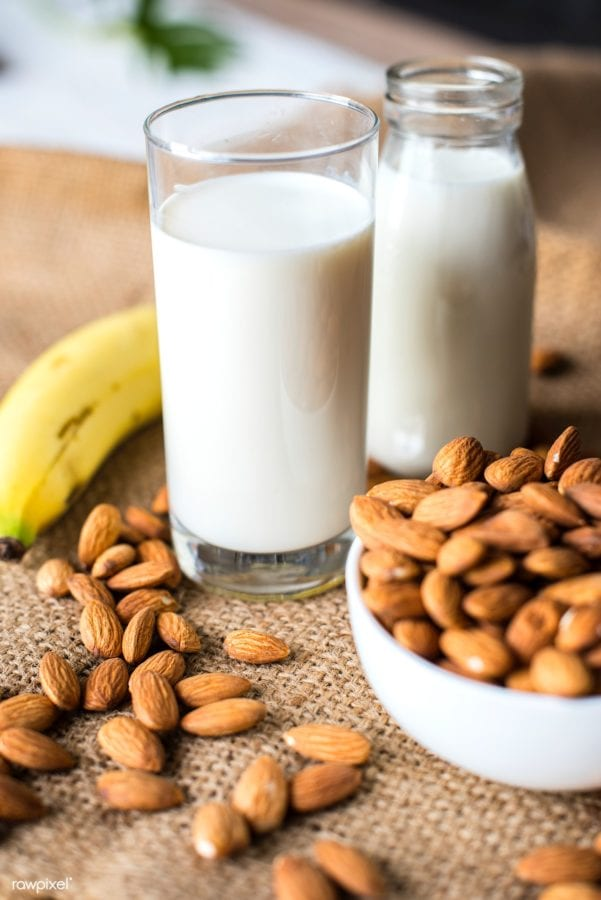 Bowl of almonds with almond milk sitting beside it and loose almonds all around.