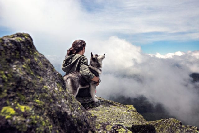 A woman with black hair sits on a rocky ledge with a husky standing beside her and her arm wrapped around it.