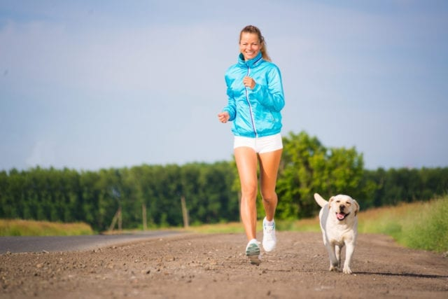 A Young Woman Running with a Dog